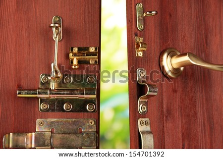 Metal bolts, latches and hooks in wooden open door close-up - stock photo