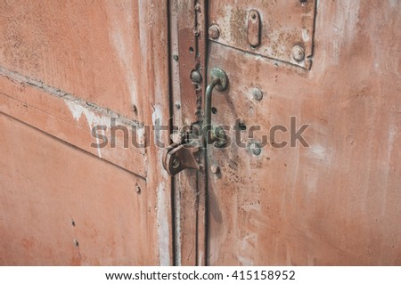 metal brown old metal door with a keyhole, closed.  - stock photo