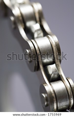 metal chain over gear - extreme macro with very shallow depth of field. focus on gear tooth near bottom right.