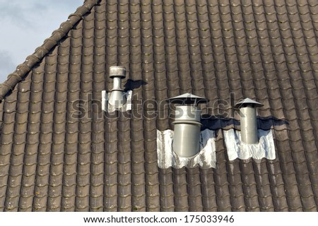 Metal chimneys - A black tiles roof with three ventilation pipes - stock photo