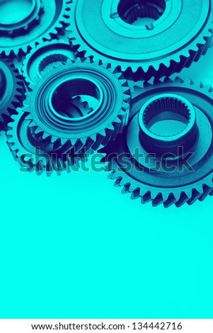 Metal cog gears bonding together on blue background - stock photo