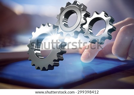Metal cogs and wheels connecting against businessman using laptop and tablet at desk - stock photo