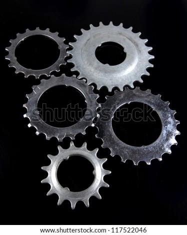 Metal cogwheels on black background - stock photo