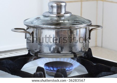 Metal cooking pot standing on kitchen stove with flame. Image with clipping path for using another backgrounds