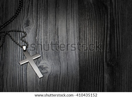 Metal cross on a wooden background - stock photo