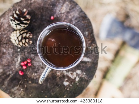 metal Cup with tea on a stump with pine cones