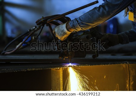 Metal cutting with acetylene torch close-up on low light - stock photo