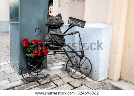 "Metal decorative statue of a cat on a bicycle with a sign ""Welcome"" and a pot with flowers"