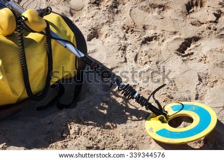 metal detector on the sandy beach - stock photo