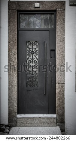 Metal door with patterns on the stone wall. Toned. - stock photo
