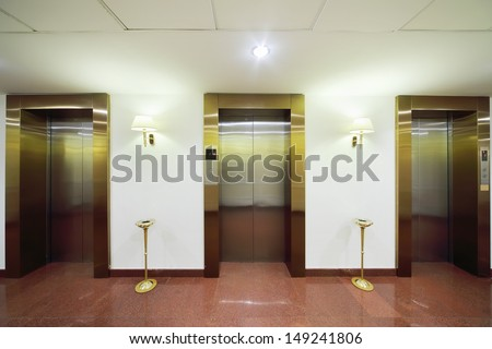 Metal doors to elevators, marble floor and high ashtrays in big stylish hotel. - stock photo