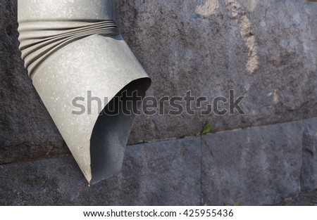 Metal downspout on the gray stone wall - stock photo