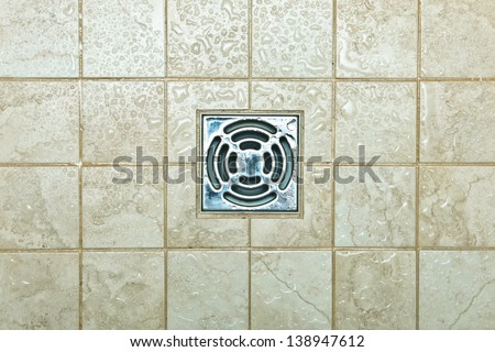 Metal drain hole in the tiled floor of a shower - stock photo