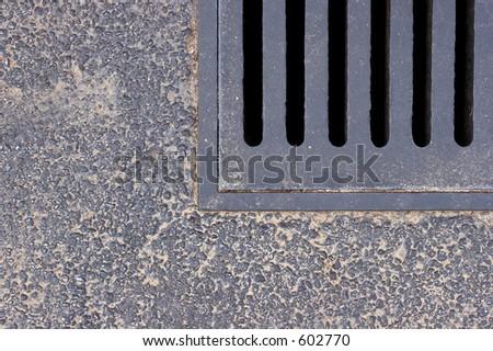 Metal drain on asphalt road. - stock photo
