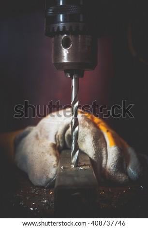Metal Drilling Works Closeup Photo. Vertical Rotating Drill Bit Closeup.  - stock photo