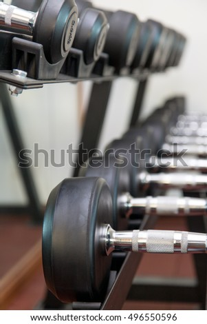 Metal dumbbells lying in a row on racks at the gym, closeup