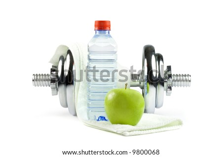 Metal dumbell with green apple, bottle of water and towel. Isolated on white - stock photo