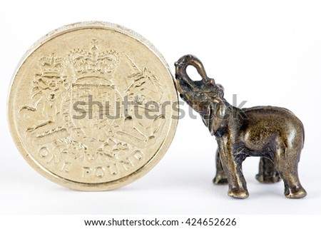 Metal elephant with one pound coin on white background - stock photo
