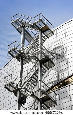 Metal exit stair on the facade of a multistory modern building of sandwich panels. Vertical view, look up. - stock photo