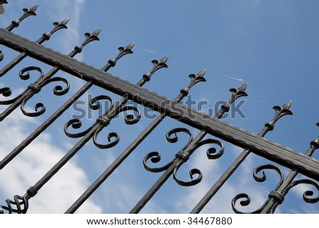Metal fence and blue sky with clouds - stock photo