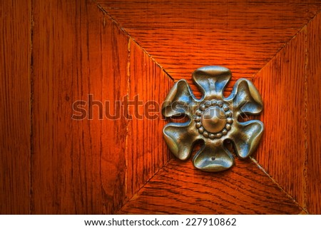 metal flower in the rustic red door - stock photo