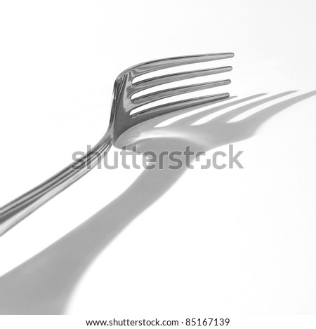 metal fork and its shadow isolated on white background