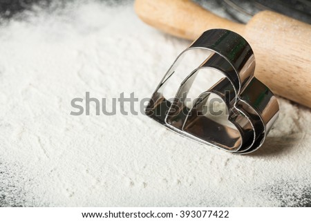 Metal forms for Christmas cookies: heart on wooden table with flour with rolling pin on table. - stock photo
