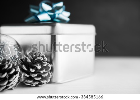 Metal gift box with blue bow and xmas baubles on white and black wooden backgrounds. Merry christmas card. Winter holidays. Xmas theme. Happy New Year. - stock photo