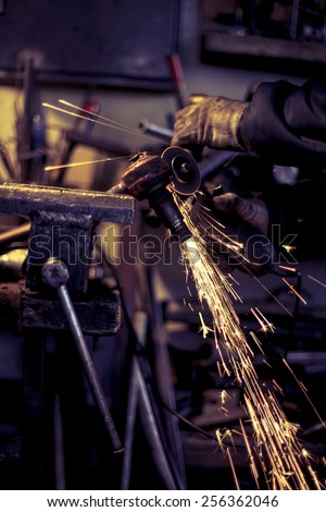 Metal grinding on steel spare part - stock photo