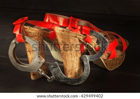 Metal handcuffs and women's shoes. The concept of sexual games. Violence against women, prostitution. Handcuffs for a sex game. Advertising sex shop.  - stock photo