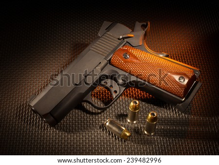 Metal handgun with wood grips and three rounds nearby
