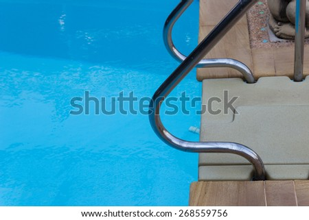 metal handrail at poolside of the swimming pool - stock photo