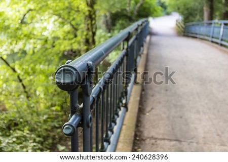 metal handrail of a bridge in a forest - stock photo