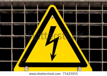 Metal high voltage danger sign bolted to steel grid - stock photo