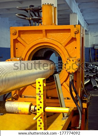 Metal hose corrugation forming machine.Manufacturing process of metallic corrugated tubes. - stock photo