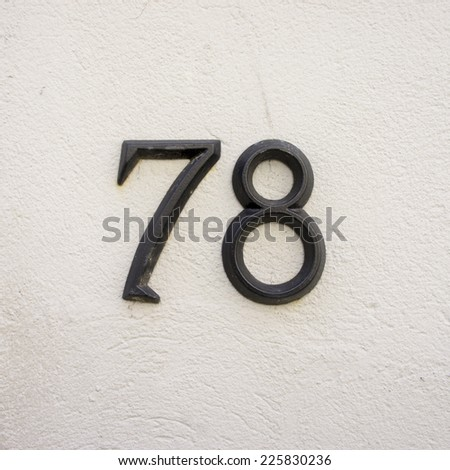 metal house number seventy eight. two separate numerals on a white stucco wall. - stock photo