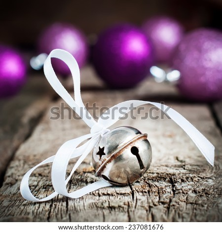 Metal Jingle Bell with star on Wooden Table with Bright Balls, Vintage Christmas Toy - stock photo
