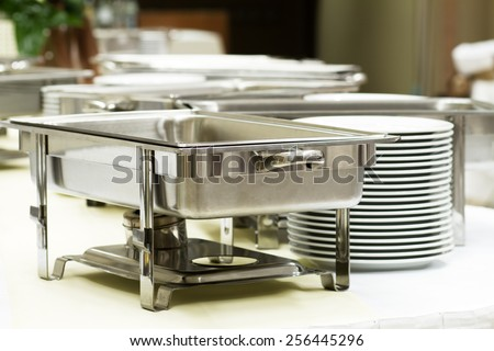 metal kitchen equipments and plates on the table - stock photo