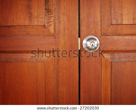 metal knob on wooden door - stock photo