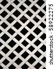 Metal lattice painted white with a black background. - stock photo