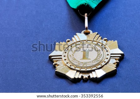 Metal medal of gold color for the winner for the first place with a ribbon of green color on a blue background - stock photo