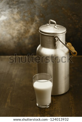 Metal milk can with a glass of fresh milk standing together on an old rustic wooden table in front of a grungy stained wall - stock photo
