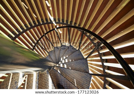 Metal modern spiral staircase details with wooden structure - stock photo