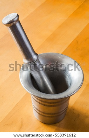 Metal mortar and pestle on wooden background texture.