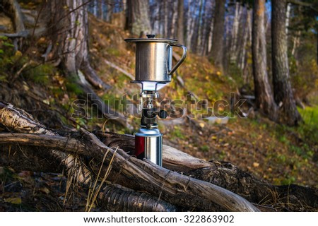 Metal mug on a gas burner between the roots of pine trees in the forest.
