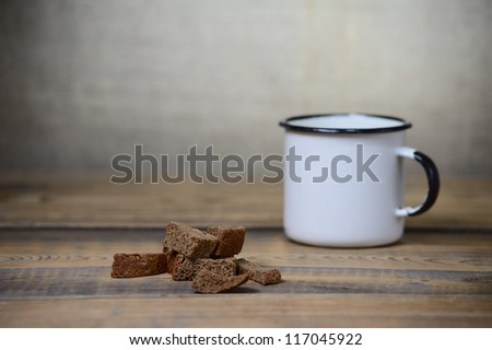 metal mug, rusks on coarse wooden table - stock photo