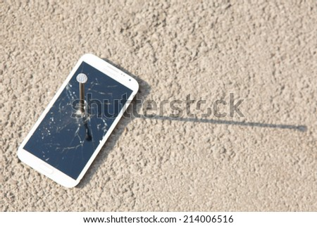 metal nail and smart phone with a broken screen over the stone surface - stock photo