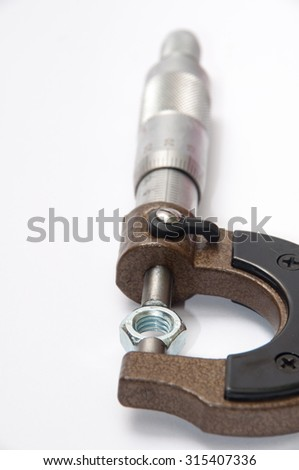 Metal nut tightened in micrometers. - stock photo