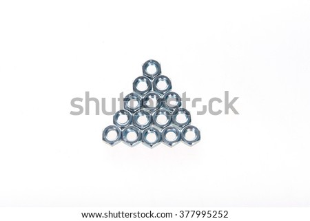Metal nuts laid out in the form of a triangle on a white background