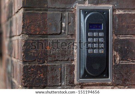 Metal on-door speakerphone on a brick wall - stock photo